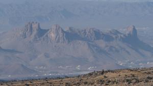 weit unter uns die Stadt Al Hamra mit den markanten Felsformationen, hinter denen wir am Vortag noch unser Zelt abgebaut hatten